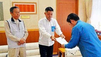 辞職要求書を受け取る松本哲治浦添市長(右)=27日、浦添市役所