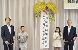 熊本県水俣市の水俣病資料館の入場者が100万人を突破、記念式典でくす玉を割る西田弘志市長(左)と緒方正実さん(右)たち=22日午後