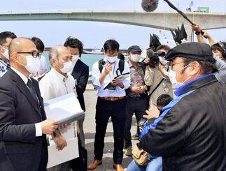 県の松田了環境部長(左)に早急な対策を求める上野自治会の金城武信会長(右)=14日午後、浦添市・牧港漁港