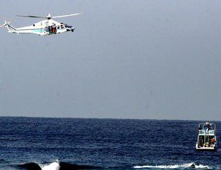 救出直後の現場付近。那覇海上保安部のヘリ(左上)から男性をダイビング船(右下)に引き渡された=日午前時分、北谷町宮城海岸沖(安里駿佑君提供)