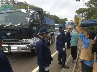 ボードを掲げて工事車両の進入に反対する市民ら=14日午前9時半ごろ、東村高江
