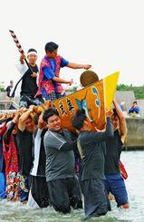 奥武島海神祭の本バーリー七番勝負を制し、フニウドゥラシェーで勝ちどきを上げる「西」のこぎ手ら=1日、南城市玉城奥武