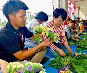 心を込めて花冠を作るボランティア=18日午後、宮古島市総合体育館前