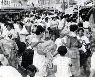 旧盆の買い物客でにぎわう那覇市の平和通り。大八車も立ち往生する人だかりだった=1962年8月11日
