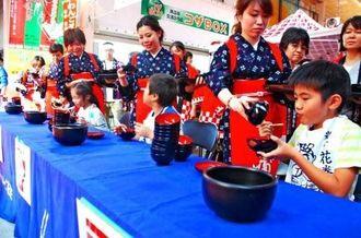 小学生の部で次々とそばを平らげるこどもたち=13日、沖縄市一番街商店街
