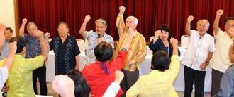 活動の強化を目指しガンバロー三唱で気勢を上げる辺野古基金総会の参加者=13日午後、那覇市・サザンプラザ海邦