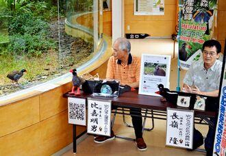 記者会見で協力を呼び掛けるどうぶつたちの病院沖縄の長嶺隆理事長(右)とやんばる地域活性サポートセンターの比嘉明男理事長(左)。生態展示学習施設のヤンバルクイナ「クー太」(左端)も会見をのぞいた=3日、国頭村安田