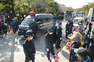 米軍北部訓練場のヘリパッド建設に市民が抗議する中、警察車両の先導で基地内に砂利を運ぶ車両=25日午前9時25分ごろ、東村高江