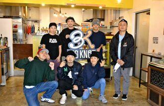 上門百代代表(前列右から2人目)とスタッフら。隣にはオリジナルやセレクトしたストリート系ファッションを扱う店舗がある=25日、北谷町北谷