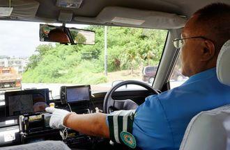 タクシー配車サービス「DiDi」システムを操作するタクシー運転手=20日、豊見城市