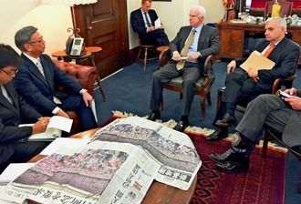 5・17県民大会を報じた地元紙を広げ、マケイン氏(右から2人目)やリード氏(右端)に反対の声を届ける翁長雄志知事(左から2人目)=2日、米ワシントンの上院議員会館