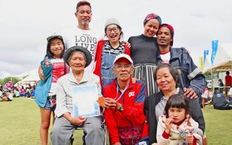 完走後、叔母の仲地ヨシ子さん(前列左)と子や孫らに祝福される上江洲智一郎さん(同中央)=27日、久米島町営仲里野球場