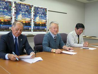 コンベンションの開催を報告する実行委員長の江川ゲンタさん(中央)=宮古島市役所