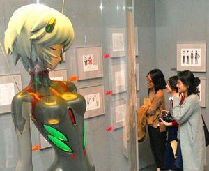 エヴァンゲリオン展の内覧会で原画に見入る関係者ら=24日午後、那覇市おもろまちの県立博物館・美術館