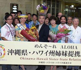 空港で歓迎を受けるデービッド・イゲ米ハワイ州知事(中央)とドーン・アマノ・イゲ夫人(同右)=7日午後9時すぎ、那覇空港