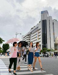 蒸し暑い日が続き、日傘を手に歩く観光客ら=3日、那覇市・県庁前