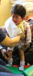 心臓移植手術後、ぐずりながら立つ訓練をする翁長希羽ちゃん=米コロンビア大学病院(両親提供)