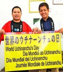 早くも「ウチナーンチュの日」をPRする横断幕を作った比嘉さん(左)と伊佐さん=沖縄タイムス北部支社