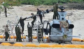 不時着したUH1ヘリのローターを取り外す米軍関係者=7日午後0時50分、うるま市・伊計島(金城健太撮影)