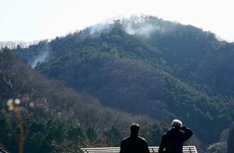 栃木県足利市の山林火災で発生した煙を見つめる人々=27日午後