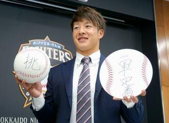 契約更改を終え、写真撮影に応じる日本ハムの吉田輝星投手=18日、千葉県鎌ケ谷市