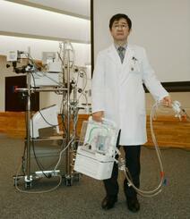 国立循環器病研究センターの開発者が手にする新型の人工心肺装置と従来型のもの(左)=10日午後、大阪府吹田市