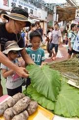 仏壇への供え物などを買い求める客でにぎわう市場=14日午後、那覇市・第一牧志公設市場
