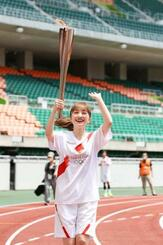 トーチを掲げて走る聖火ランナーの百田夏菜子さん=23日午後、静岡県袋井市(代表撮影)