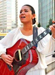 ギター1本で全国各地を訪ね歌声を聞かせているカワミツサヤカ=東京・銀座の路上