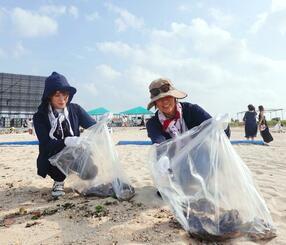 花火ショーの翌朝、ビーチのごみを拾うボランティア=17日、宜野湾市の宜野湾トロピカルビーチ