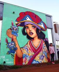 路上アートフェスティバルで描いた作品「ハナガサヒネ」の前に立つレミ・ミードさん=ホノルル市カカアコ地区