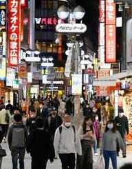 東京・渋谷の繁華街をマスク姿で歩く人たち=29日夜