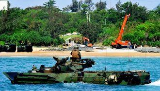 沖で水陸両用車が訓練する中、重機を使って砂浜に砂利や土砂を敷く作業が続くキャンプ・シュワブ=23日午前9時50分ごろ、名護市辺野古