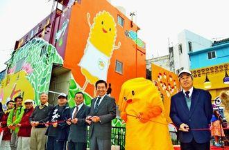 銀天街前の巨大壁画の完成を祝いテープカットする桑江朝千夫市長(右から3番目)ら=1月31日、沖縄市照屋