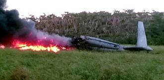 牧草地で大破し、炎上する米軍ヘリ=11日午後5時40分ごろ、東村高江(西銘晃さん提供)
