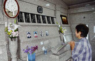 両開きの扉を開けた墓の中には、亡くなった両親やきょうだいの氏名、享年を書いた板や写真が飾られている=4日、読谷村座喜味