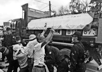 土砂を積んだダンプカーの進入に抗議する市民ら=10月25日午前、東村高江・N1ゲート前