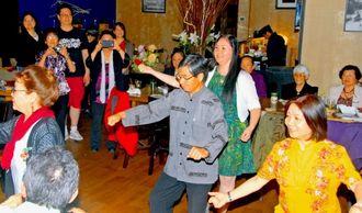 かぎやで風を踊るなどしてニューヨーク県人会の会員と交流を深める稲嶺進名護市長(中央)=17日夜(現地時間)、ニューヨーク市内