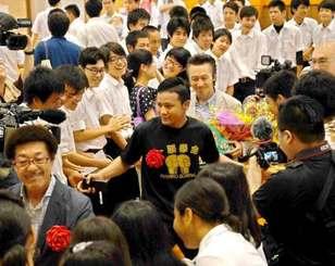 母校を訪れ、生徒の歓迎を受ける比嘉大吾選手(中央)=宮古島市・宮古工業高校体育館