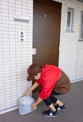 客から注文された商品を「置き配」で届ける配達員=1日、浦添市