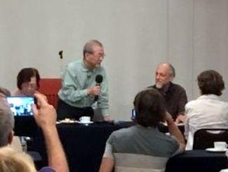 マイクを手に講演する鈴木信博士(奥左から2人目)とキュルティ博士(同3人目)=那覇市内