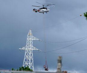 ヘリパッド建設に向け、重機を運ぶヘリ=9日、東村高江