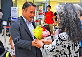 出迎えた支援者から花束を受け取る沖縄平和運動センターの山城博治議長(左)=18日夜、那覇空港