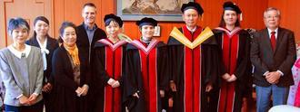 初の学位記授与式で卒業生が着るアカデミックドレスを作ったOIST在校生と読谷山花織事業協同組合、読谷村の関係者ら=9日、読谷村役場