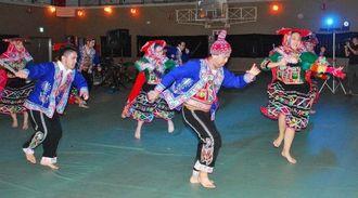 伝統衣装をつけて、ペルーの民族舞踊「ワイノ」を華麗に踊るペルーの県系人たち=21日、中城村民体育館