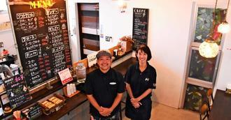 店に立つ高江洲義成さん、いろりさん夫妻。テラス席もあり、今後拡充する予定=宜野座村惣慶