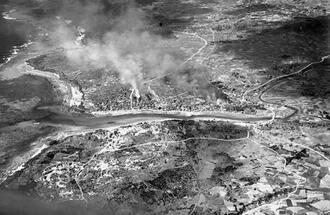 旧具志頭村具志頭に近い同村港川が炎上している様子。戦艦ワシントンの一斉射撃と空母艦載機の攻撃によって火災が生じた=1945年3月24日(県公文書館所蔵)