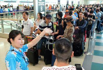 停電の影響で搭乗手続きができない利用客の行列ができた=9日午前8時半、那覇空港