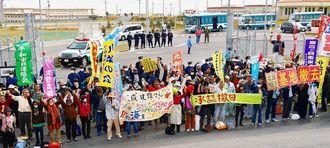 キャンプ・シュワブゲート前で抗議の声を上げる集会参加者。後方には県警機動隊、その奥には米軍の警備員や米兵らが控える=22日、名護市辺野古