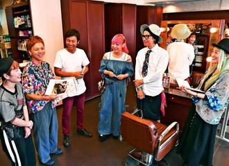 開店前のミーティング。OMUさん(右から2人目)はじめ個性的なスタッフでアイデアを出し合い、イベントなどを実現してきた=那覇市の「ミム・デ・オム」久米店